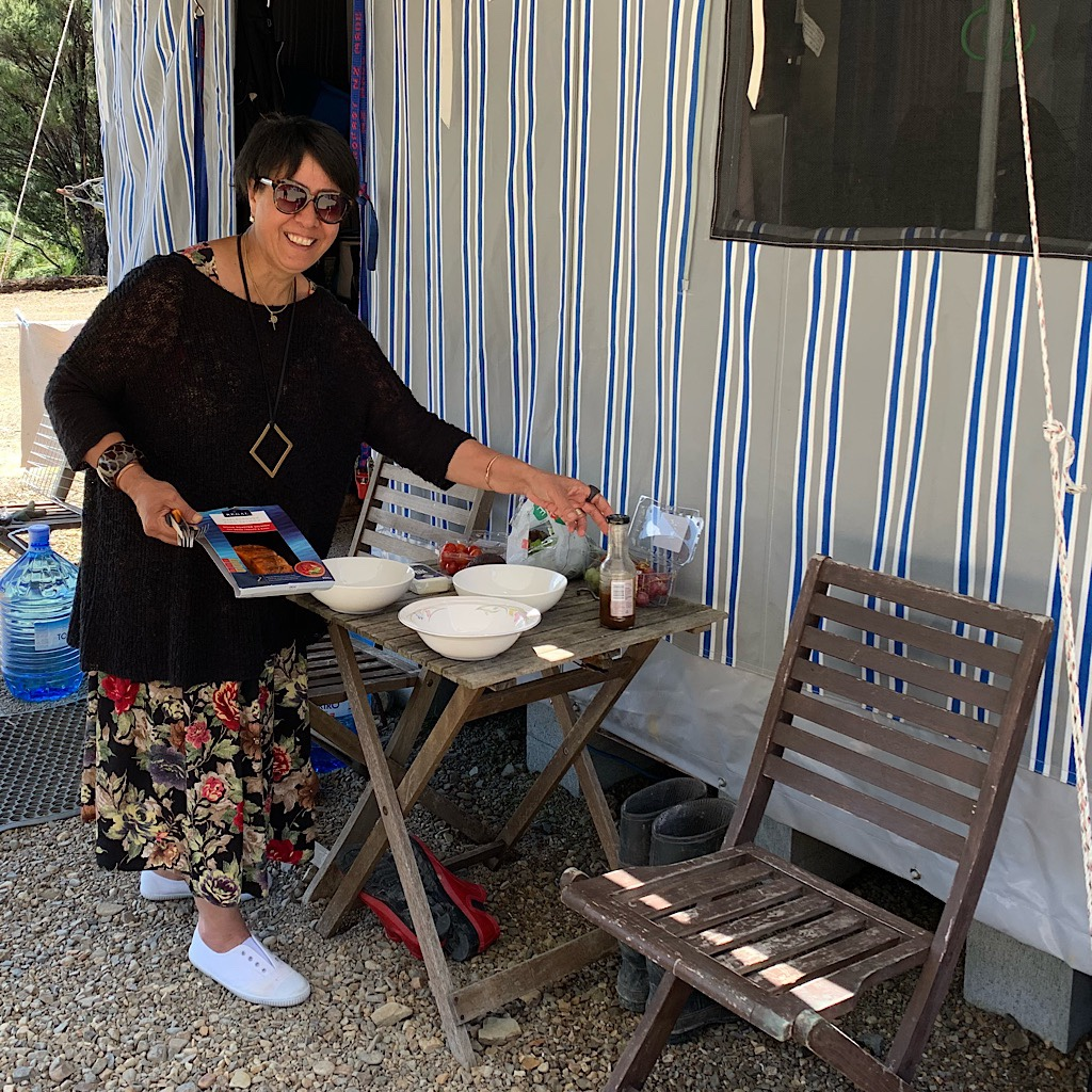Vern sets out a snack at their converted caravan high atop a hill in Kaeo.