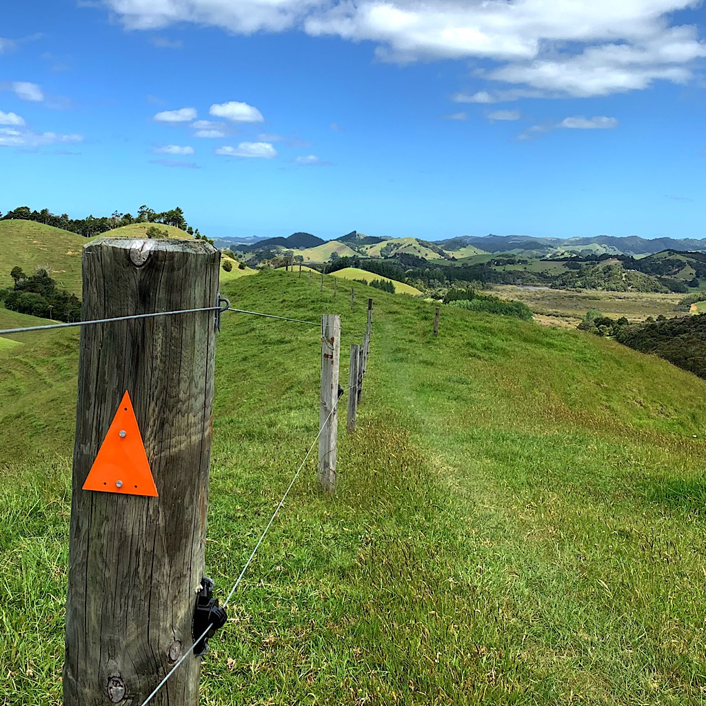 The trail follows the fence line on hilly farmland.