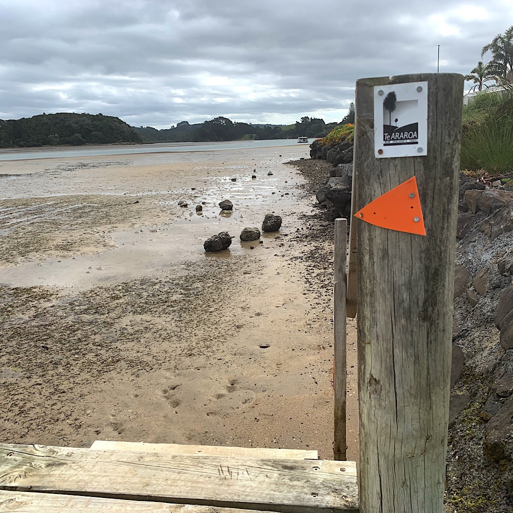 The Te Araroa sign points down stairs and to Nikau Bay, but it can only be crossed by boat.