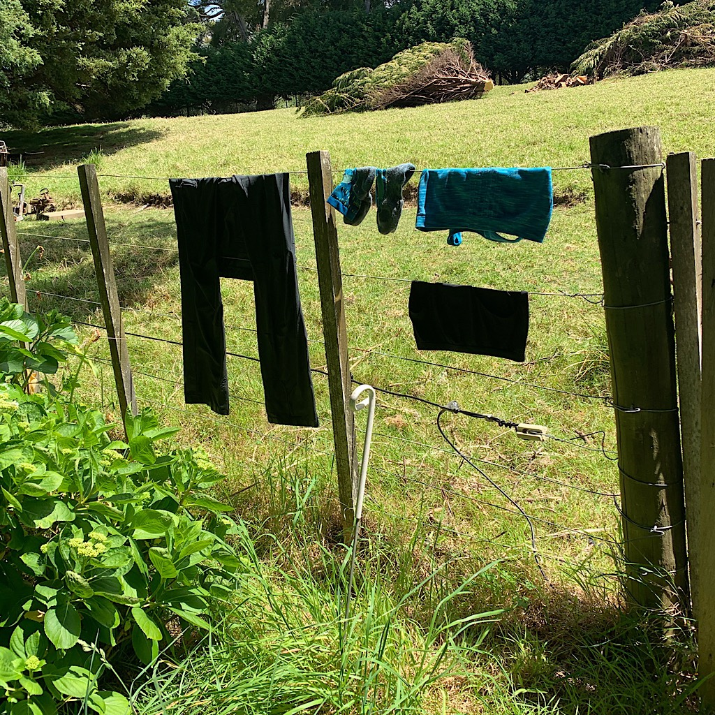 Rinsed hiking clothes drying on the electric fence at Tidesong.
