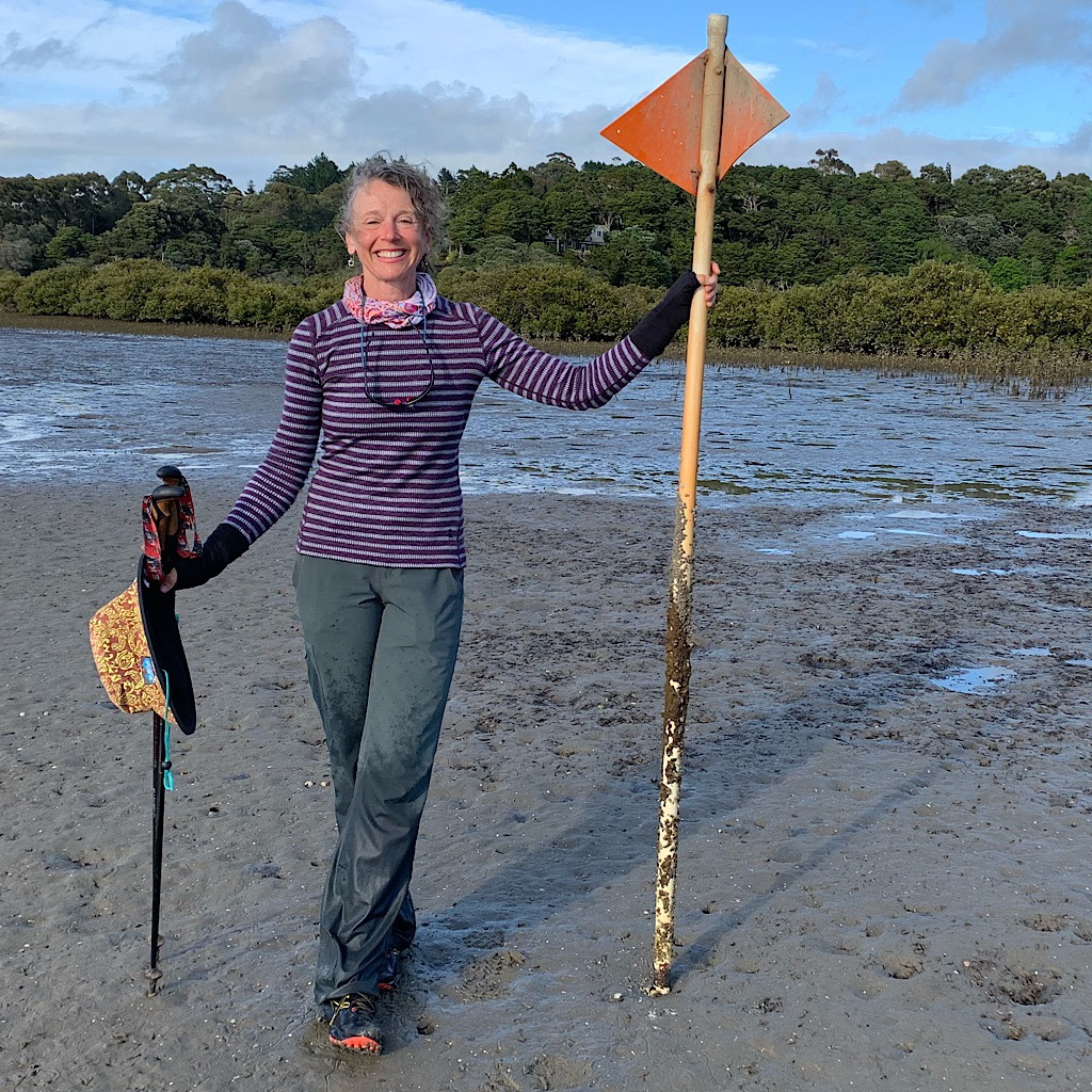 Blissful Hiker holding the TA signpost with big orange triangles pointing the way across the estuary at low tide.
