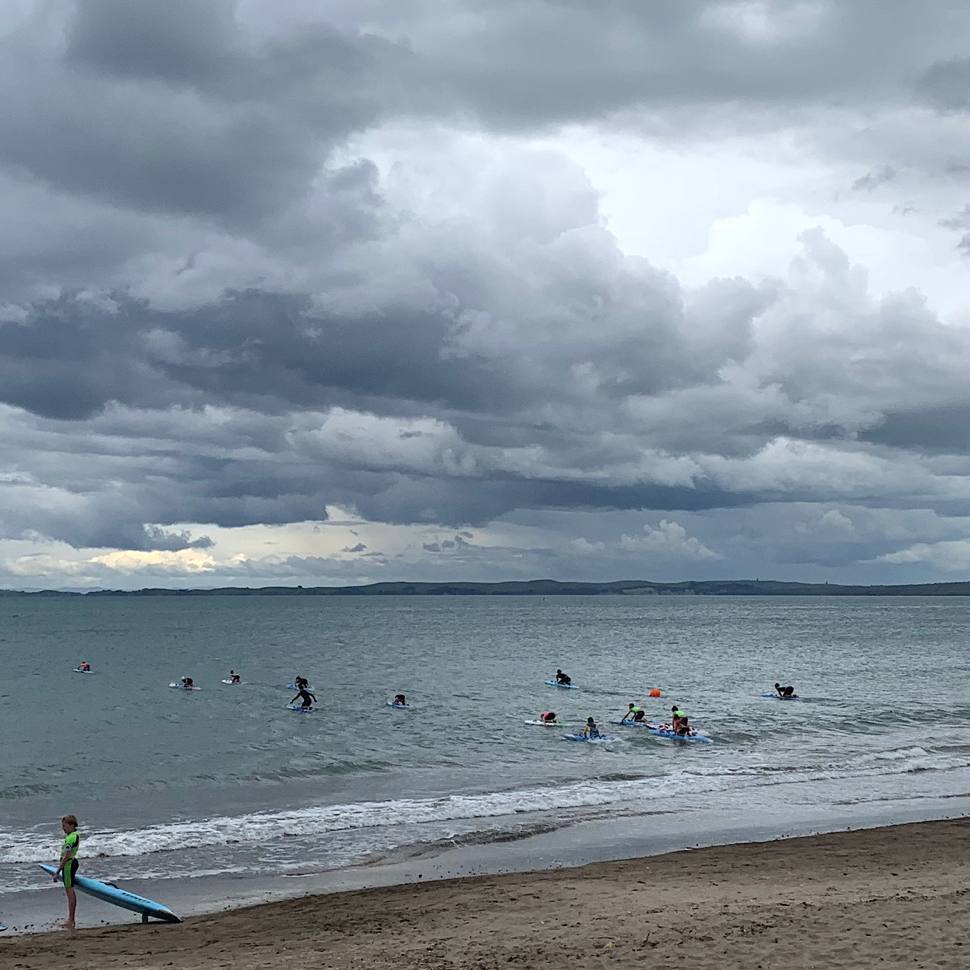 Kids taking out surf boards in one of the many bays along the North Shore. Storm clouds make no difference since it rains nearly every day.