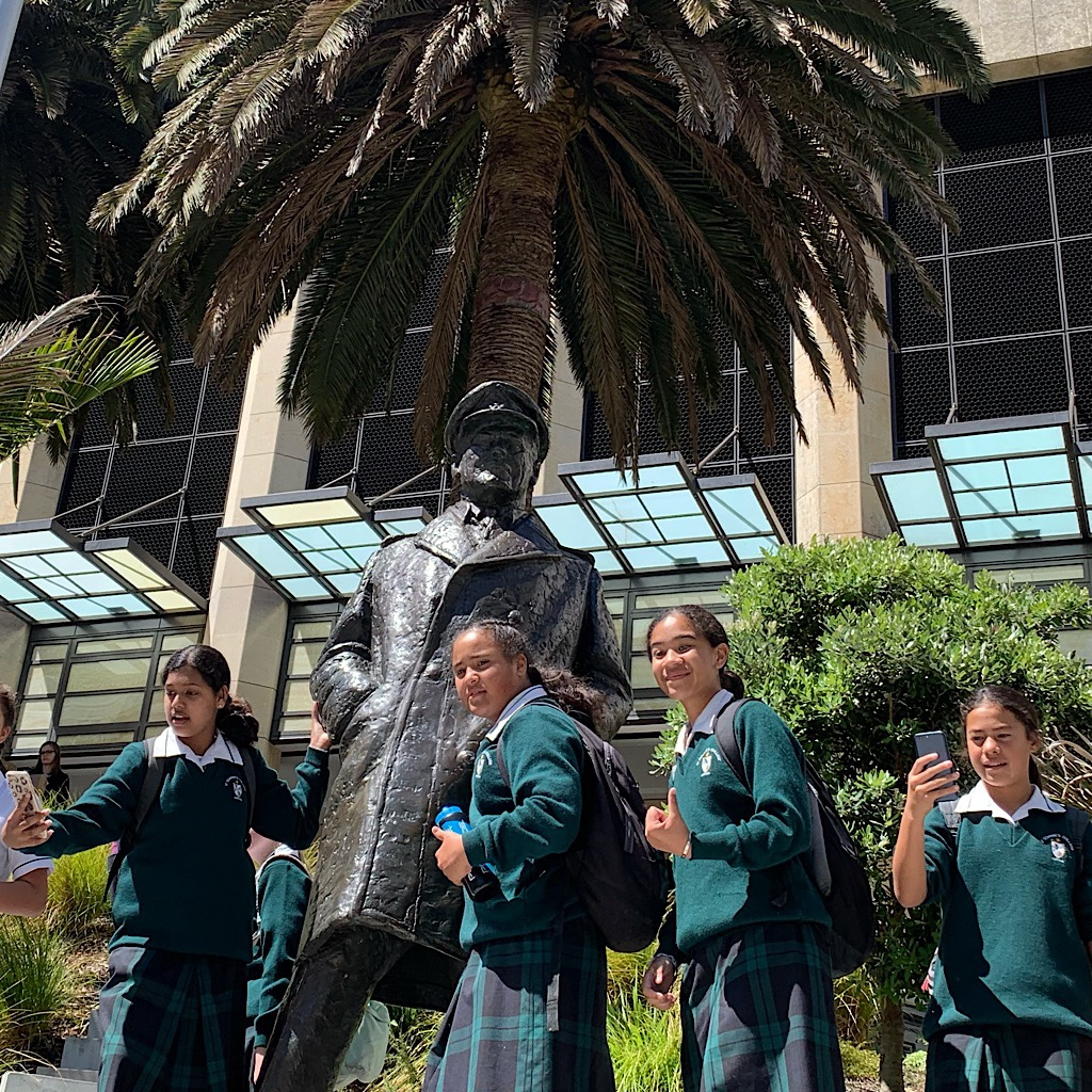 School girls take selfies next to a sea captain statue.