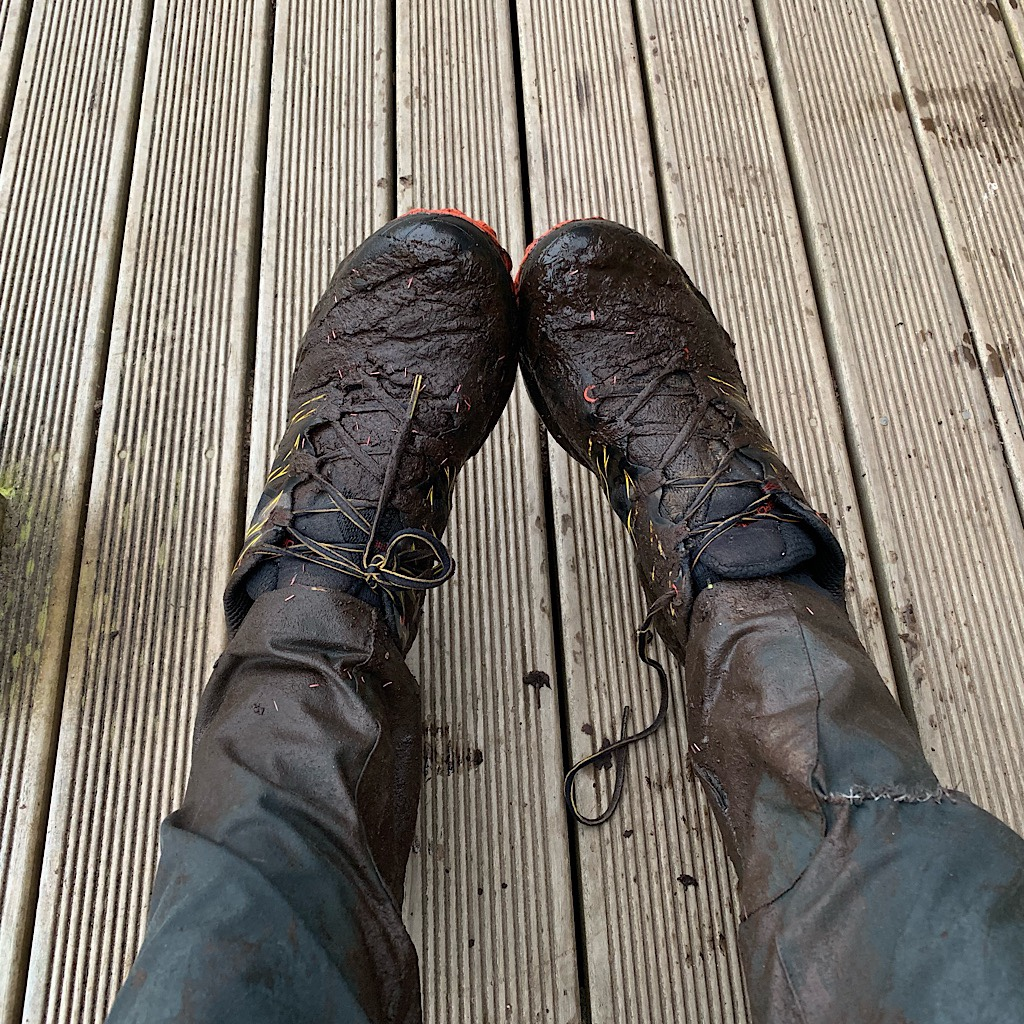 "Mud-caked shoes, socks and trousers. Fortunately the hut has a ""mud room."""