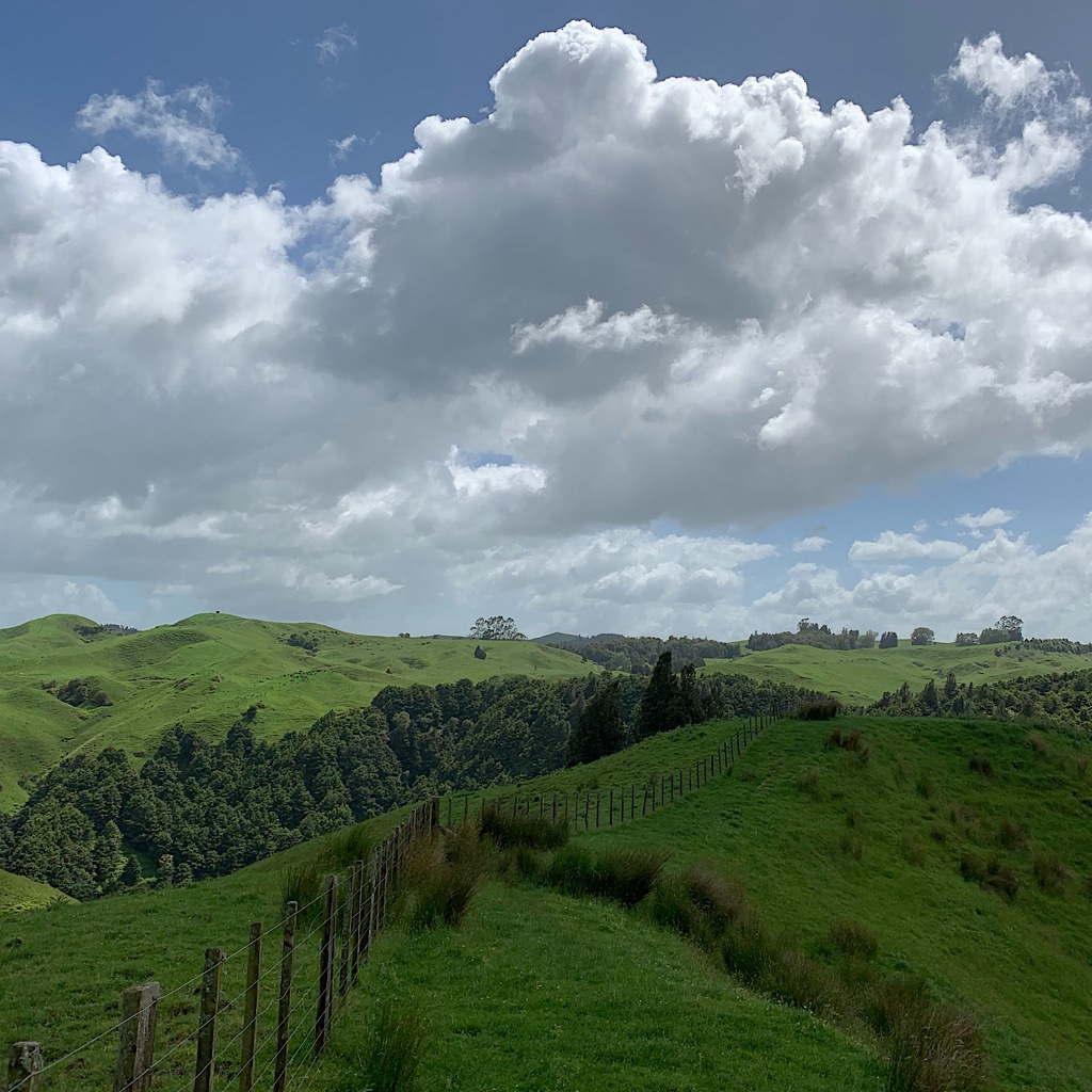 Clouds building over farmland in the King Country region of New Zealand's North Island.