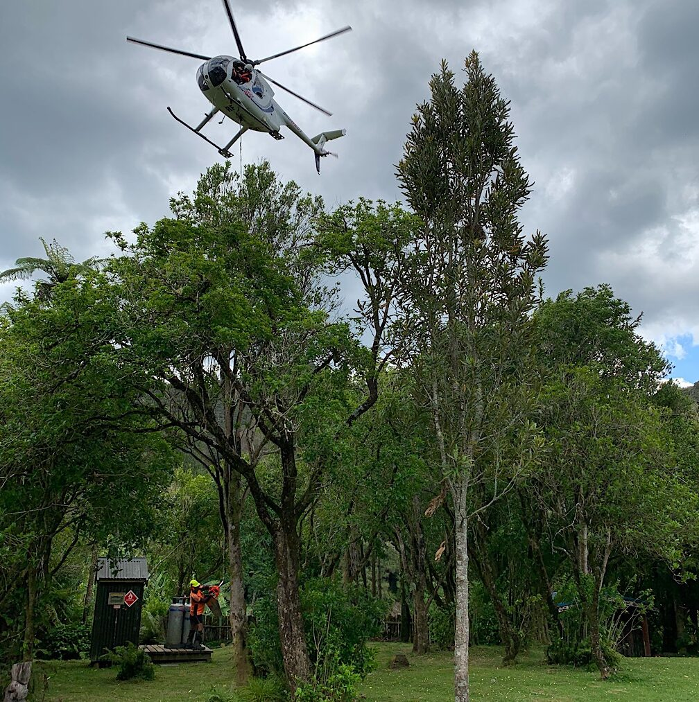 A helicopter delivers goods to the remote community including a riding lawn mower.