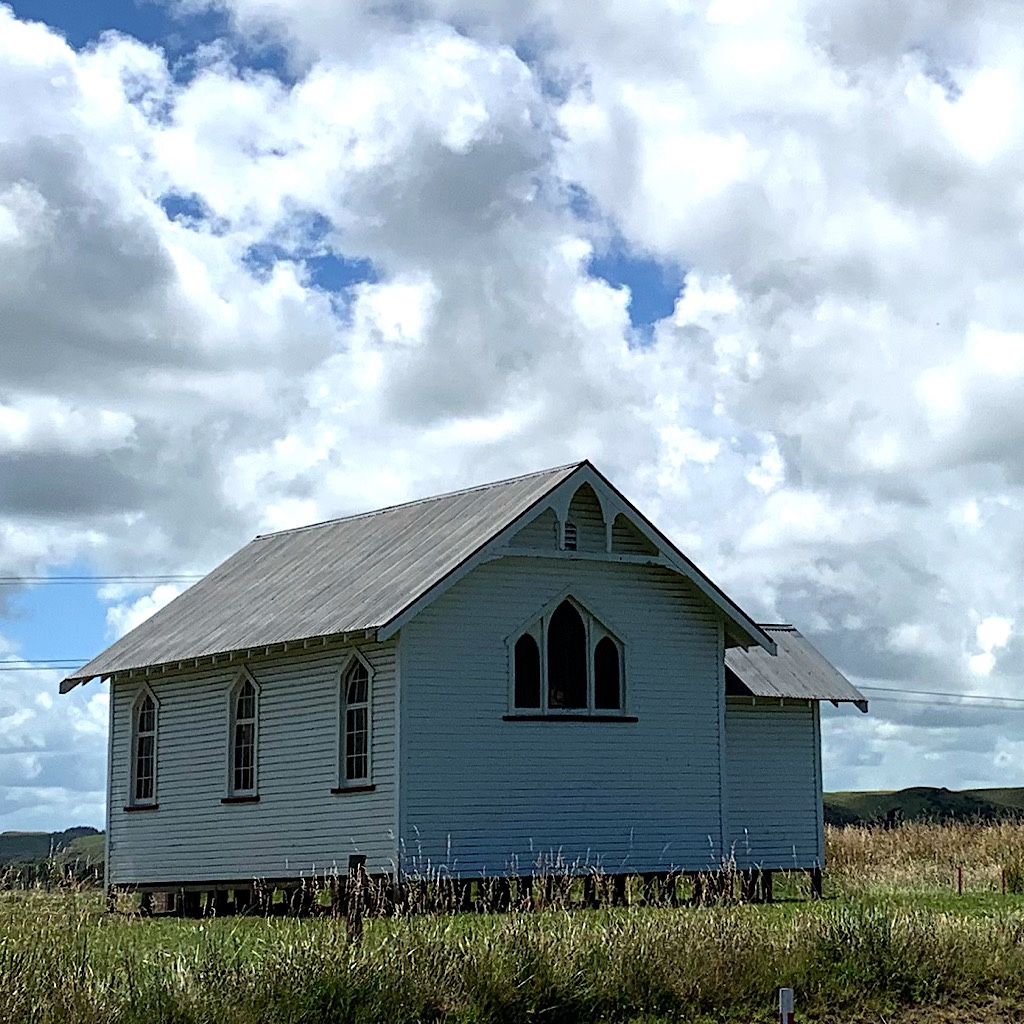 A little church on the side of the highway that looks like it could be in the Midwest of the United States.