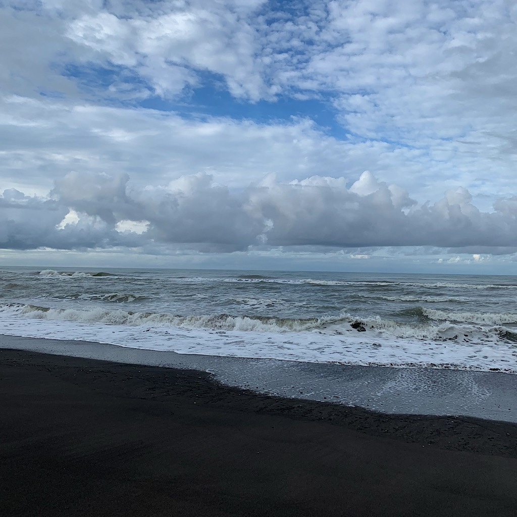 Black sand, waves, clouds.