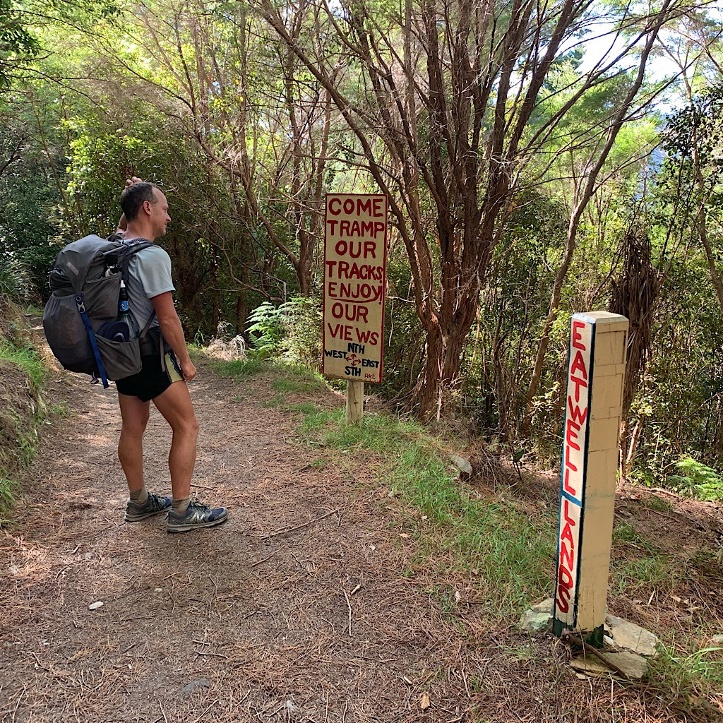 John poses in front of various signs enticing hikers to stop for  food and lodging.