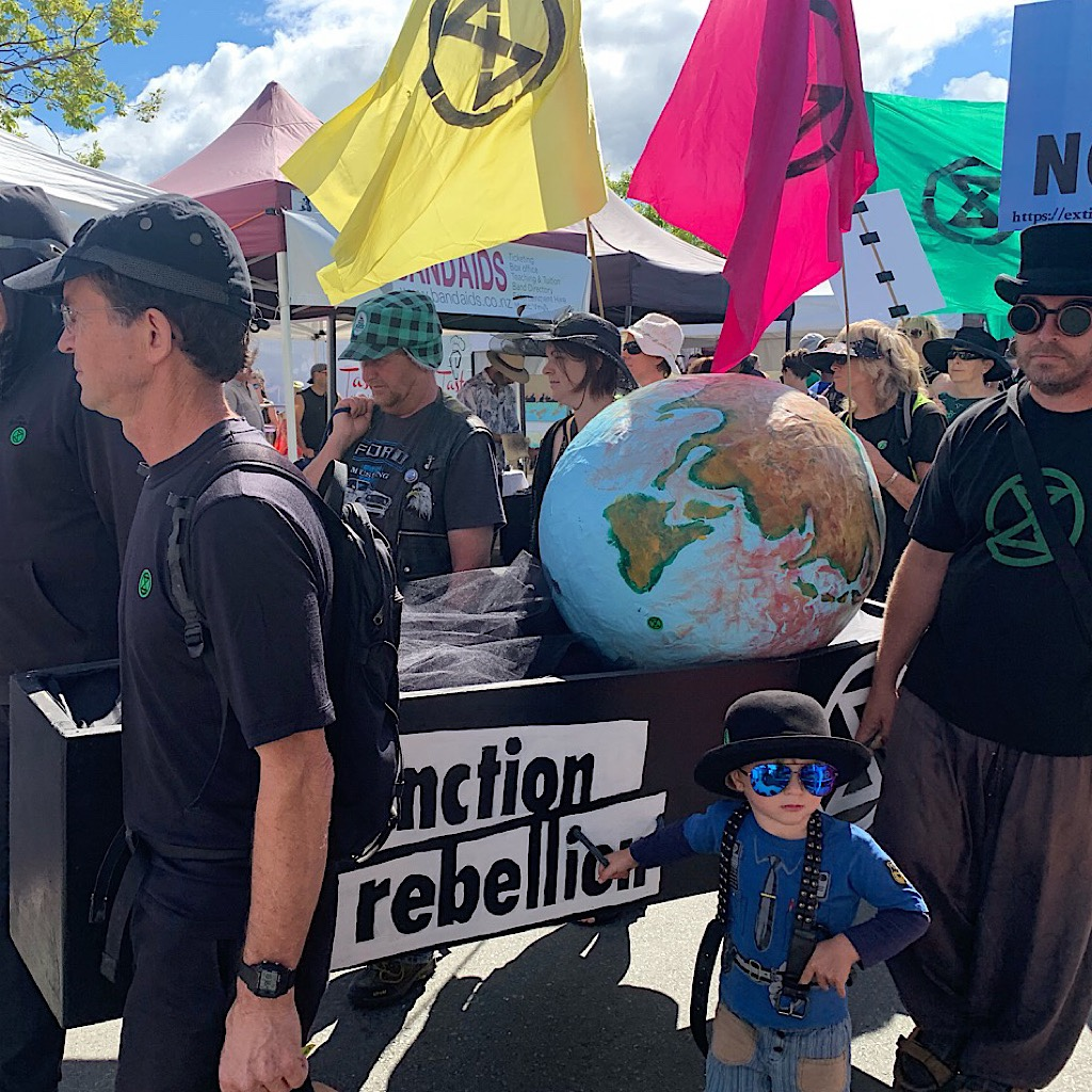 Protesters supporting green energy carrying the earth as pall bearers in the Nelson outdoor market.