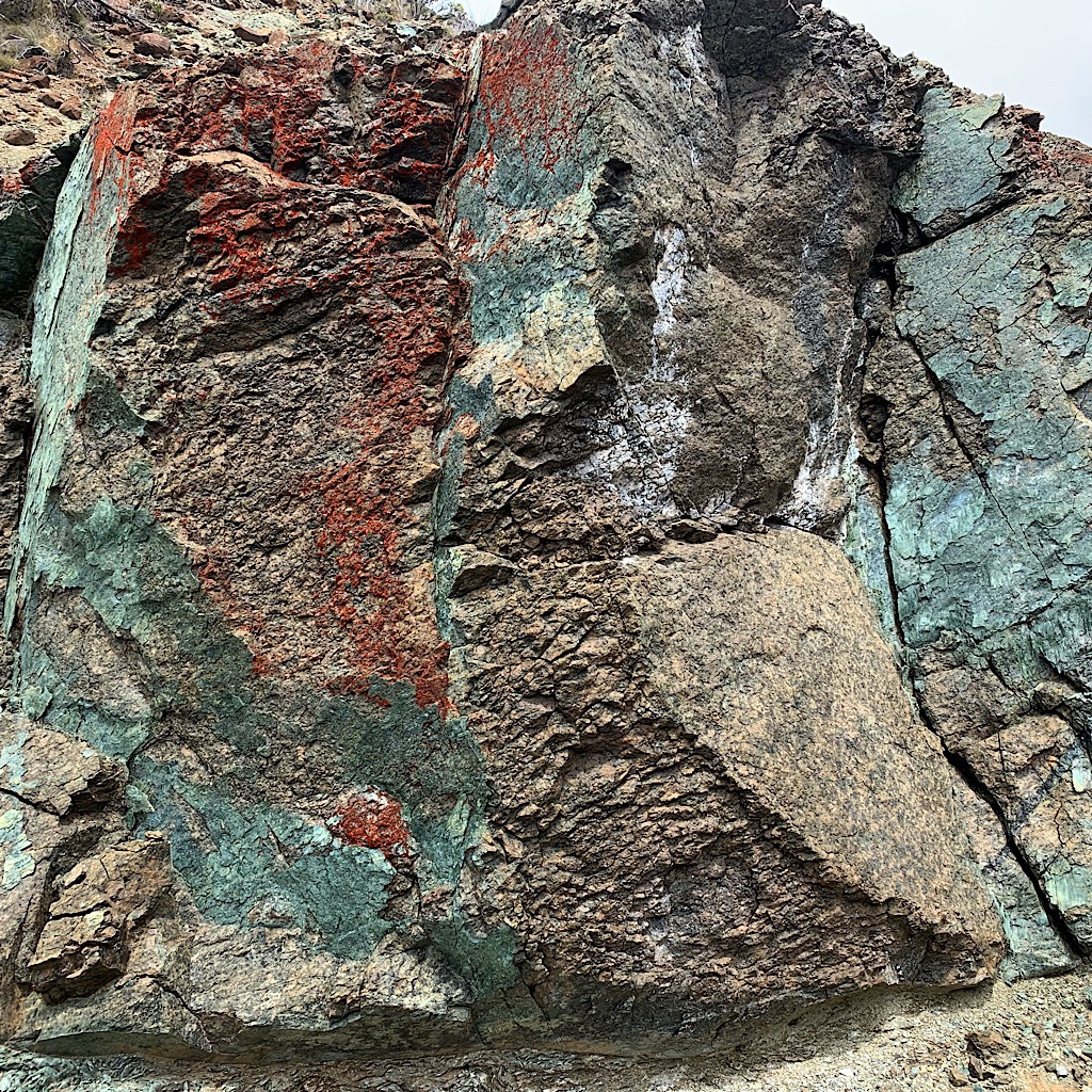 Rock shot through with brilliantly colored minerals.