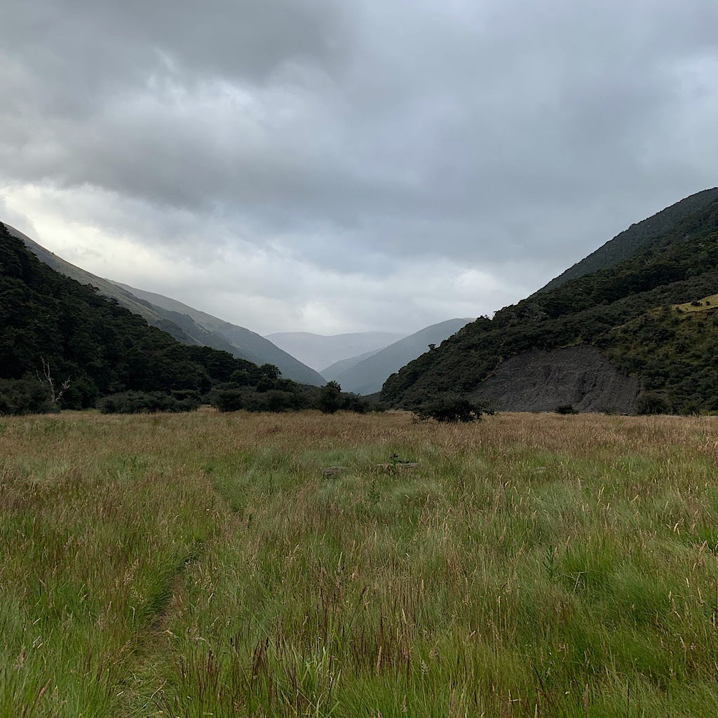 A typical view of mile after mile of grassy walk in between huge mountains, and more coming into view stacked up in the distance.