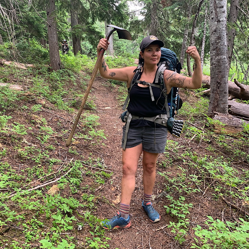 A Pacific Crest Trail worker in the North Cascades shows off her muscles and tatoos.