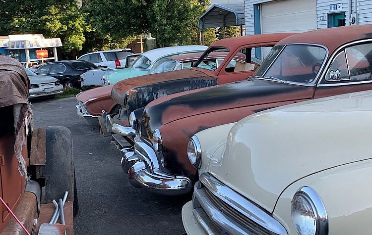 Rounded edges of 1950's cars appear like faces crowding the lot on a summer's eve.