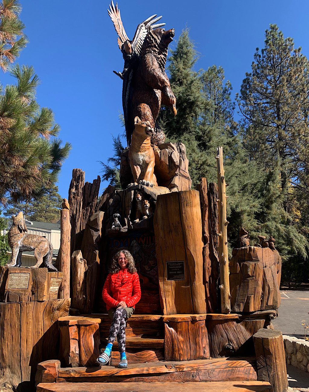 The Blissful Hiker in borrowed clothes underneath the chainsaw sculpture in Idyllwild.