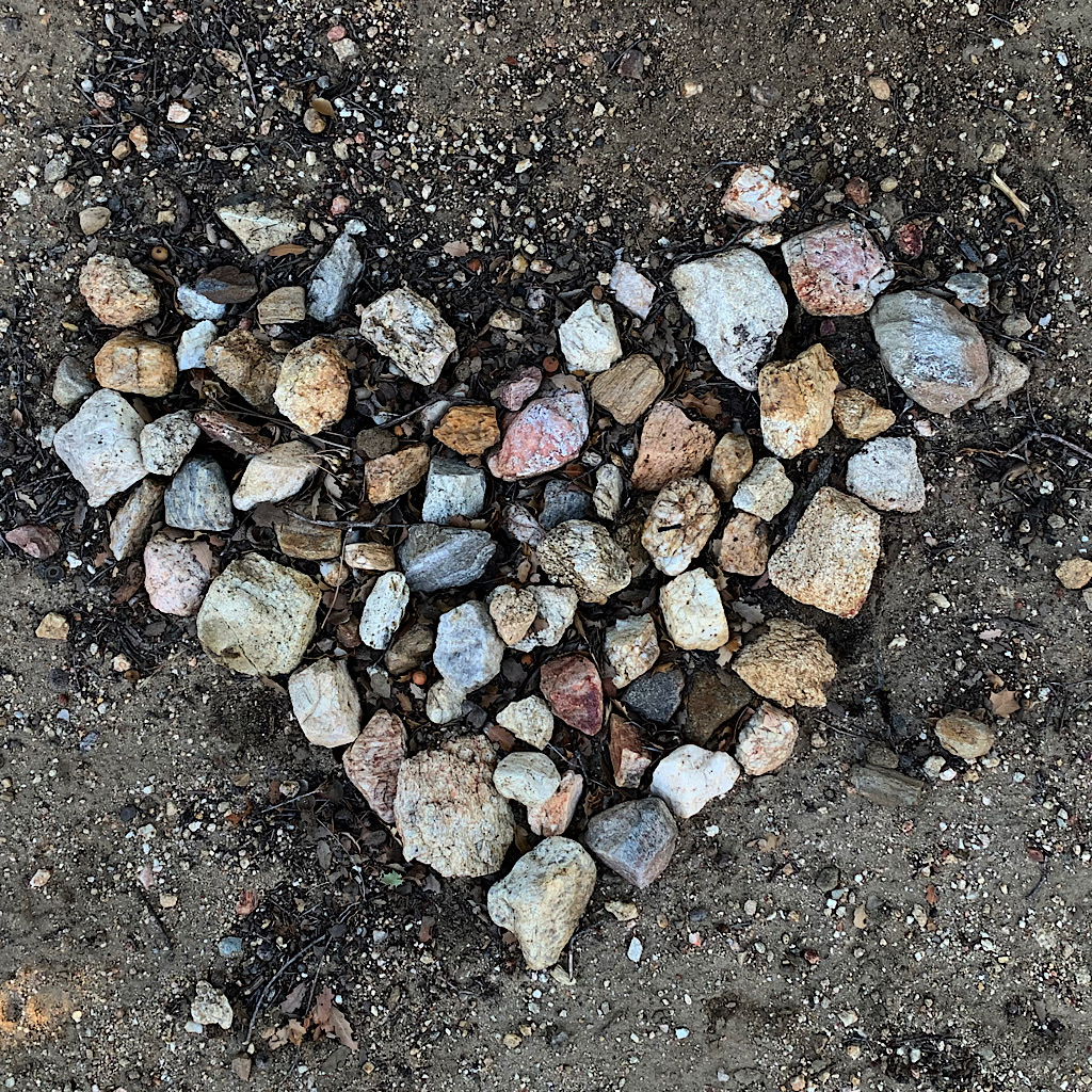 A hiker long gone leaves a heart made of collected stones.