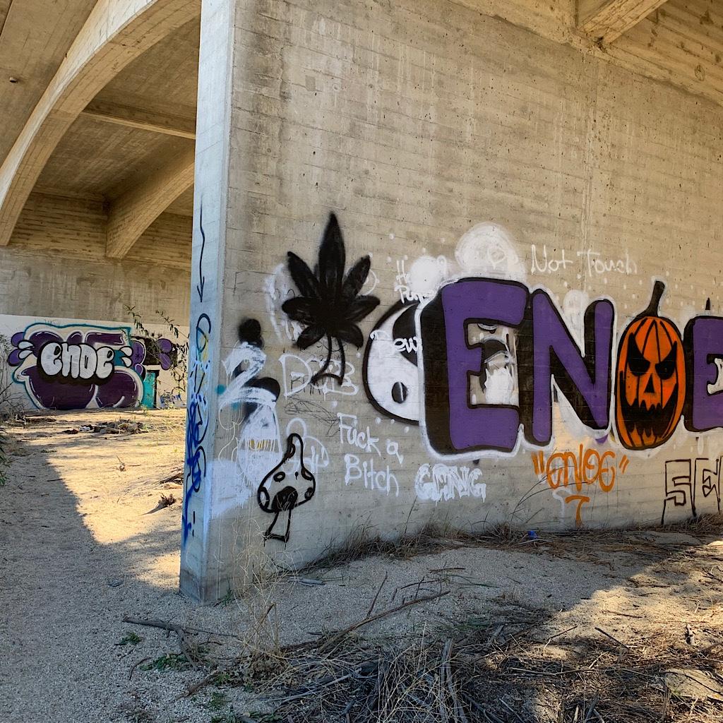 Graffiti artists tag the bridge.